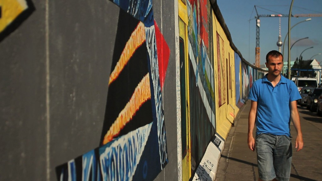 Daniele Carrer cammina di fronte alla East side gallery
