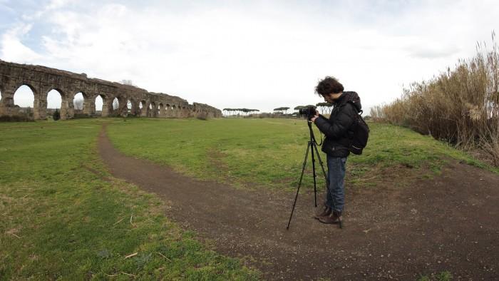 Fotografo di fronte ad un acquedotto romano.