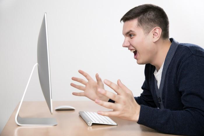 Uomo arrabbiato di fronte al computer perché Revostock ha chiuso