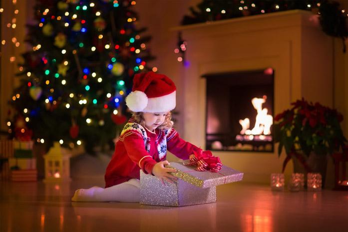 Bambina che apre i regali di Natale sotto l'albero