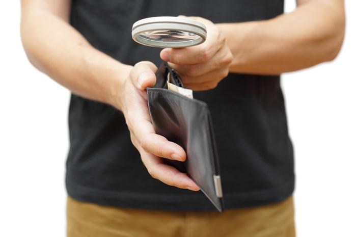 Uomo guada il suo portafogli con la lente di ingrandimento