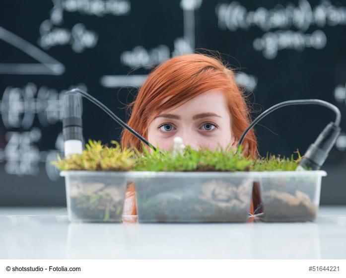 Giovane donna che guarda un vaso d'erba coltivata