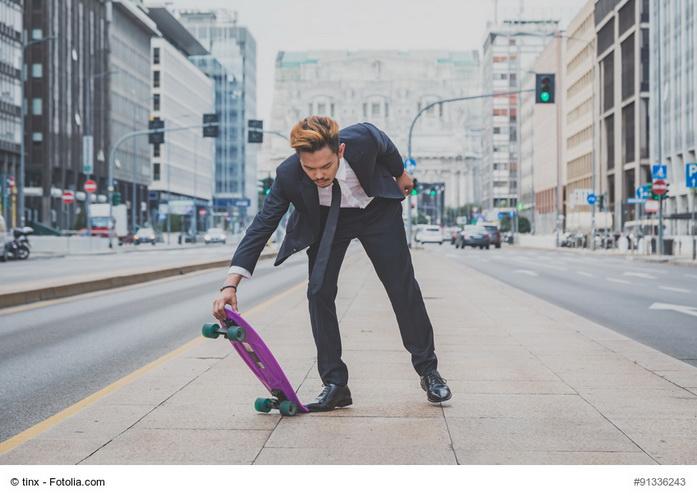 Colletto bianco che usa lo skateboard in città