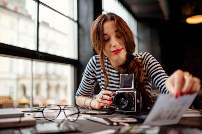 Giovane donna in ufficio con la macchina fotografica