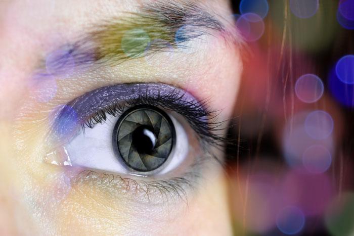 Donna con riflesso il diaframma di un obiettivo su un occhio