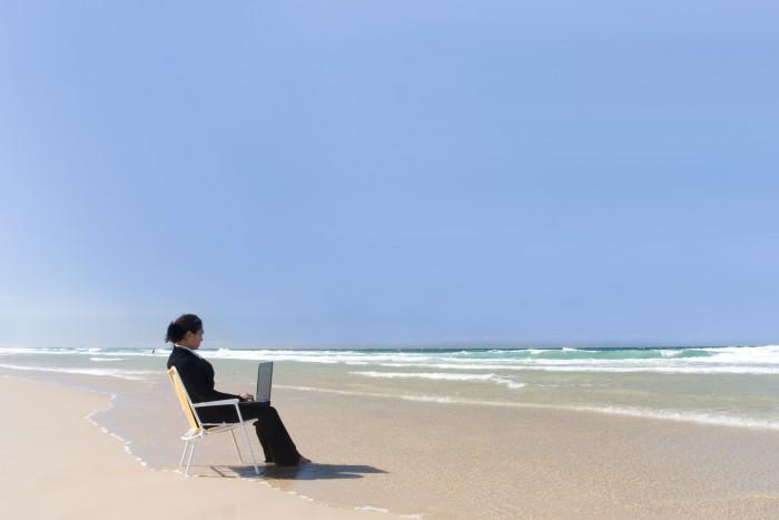 Persona che lavora con il notebook in riva al mare