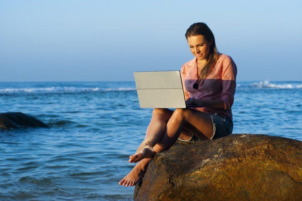 Donna in spiaggia con un computer portatile