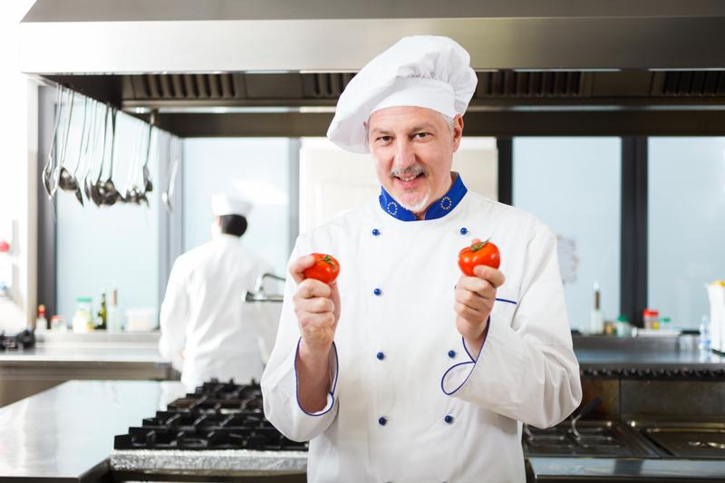 Esempio di immagine stock di un cuoco in cucina con due pomodori in mano