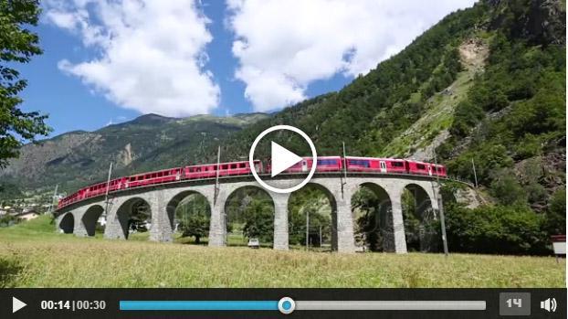 Treno rosso che passa su un viadotto alpino.