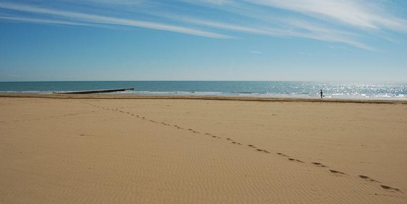 Fotografia stock di una persona che corre sulla spiaggia di Jesolo