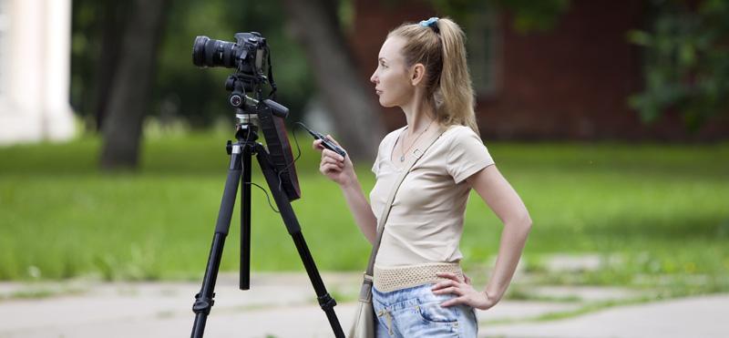 Giovane donna videomaker mentre riprende con una reflex e un cavalletto