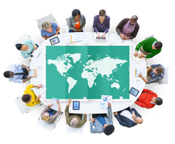 Persone di fronte ad una scrivania che mostra una cartina del mondo