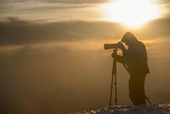 Fotografo di paesaggi al lavoro nella nebbia