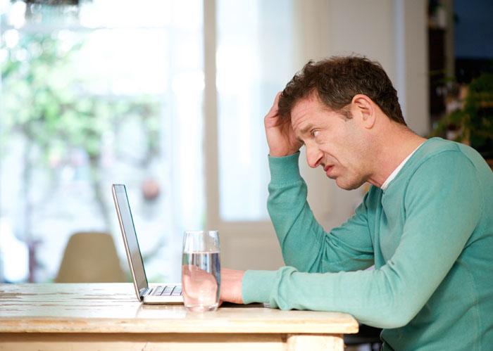 Uomo confuso di fronte al laptop