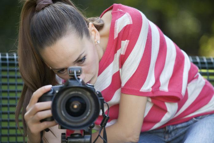 Giovane donna videomaker mentre riprende con la reflex