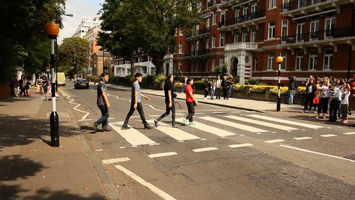 Persone che riproducono la camminata dei Beatles nell'album Abbey road