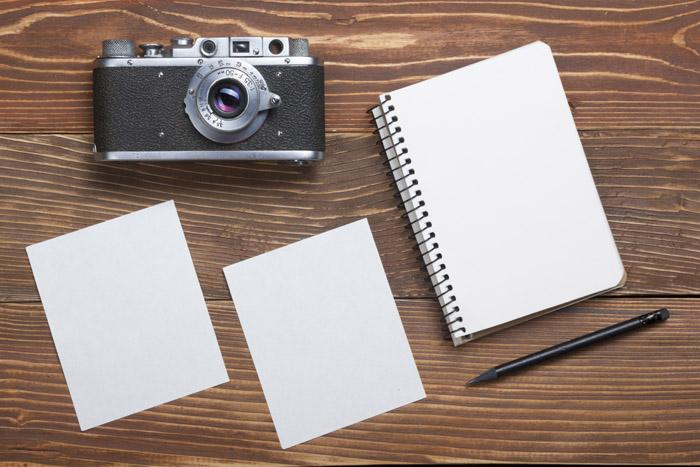 Macchina fotografica appoggiata sul tavolo con dei block notes
