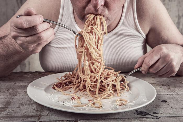 Uomo grasso che mangia spaghetti