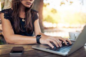 Giovane donna mentre lavora al laptop inviando foto ad un sito di microstock