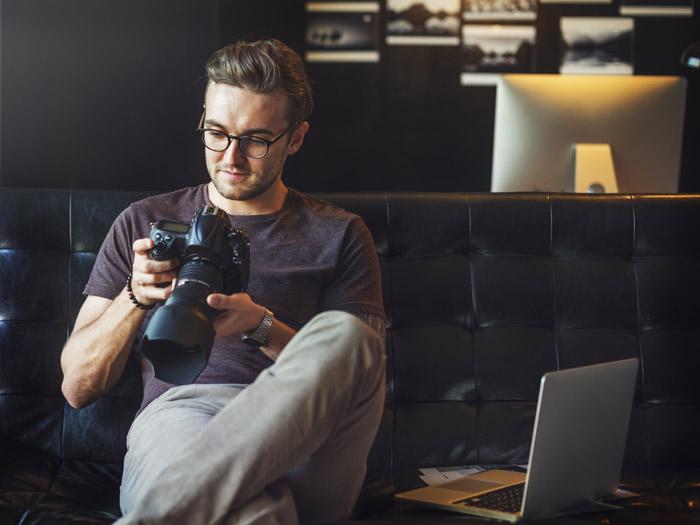 Fotografo che guarda le immagini che ha scattato sulla sua reflex