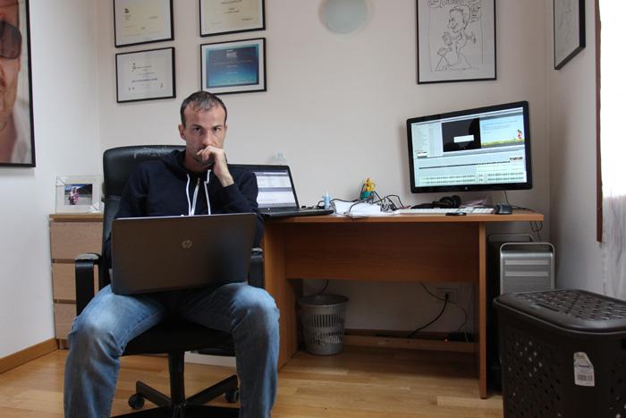 Daniele Carrer nel suo studio con un computer portatile