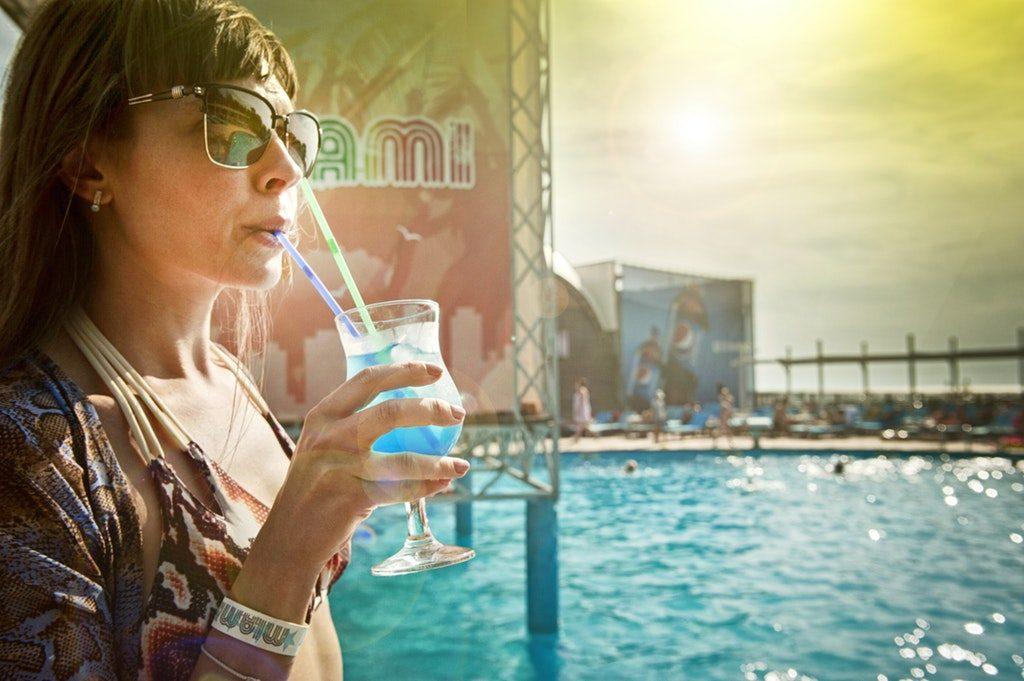 Donna che beve un cocktail sul bordo di una piscina