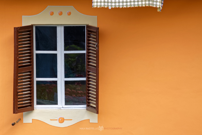 Balcone aperto su un muro arancione di Max Rastello