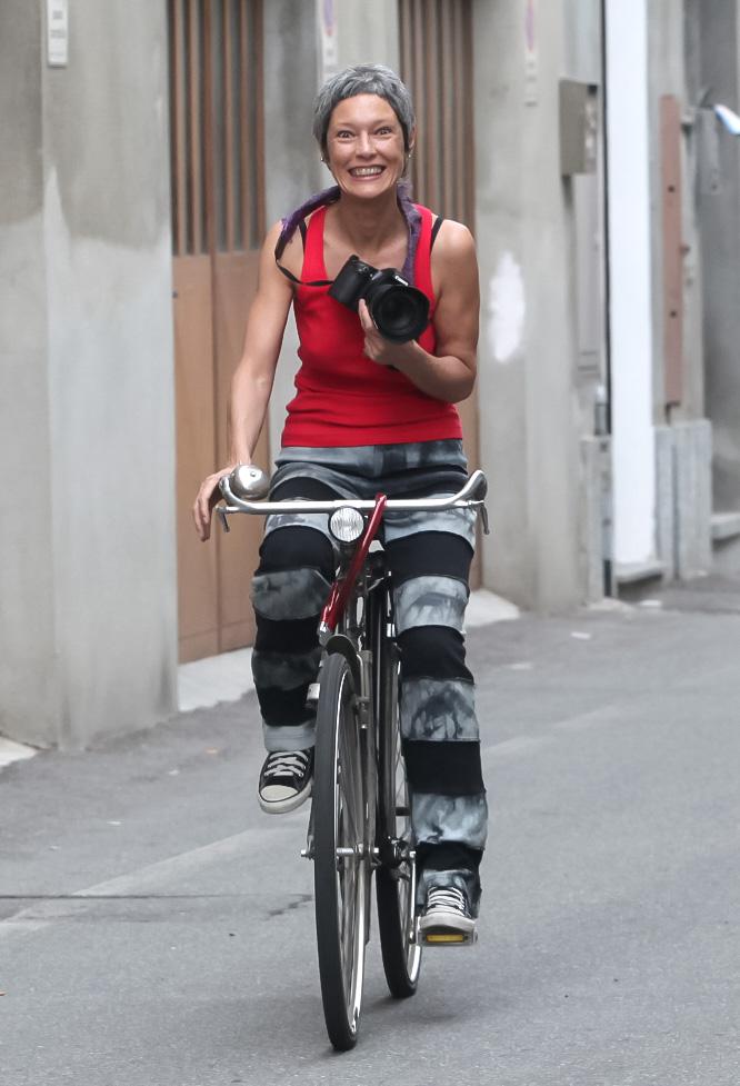 La fotografa Valeria Gilardi in bicicletta con la reflex mentre va nel suo negozio di fotografia