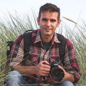 Il fotografo Fabiano Strapazzon in una spiaggia con la reflex in mano