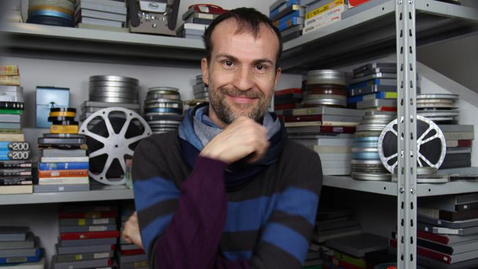 Daniele Carrer nel suo studio di fronte alla sua collezione di film 8 mm e super 8