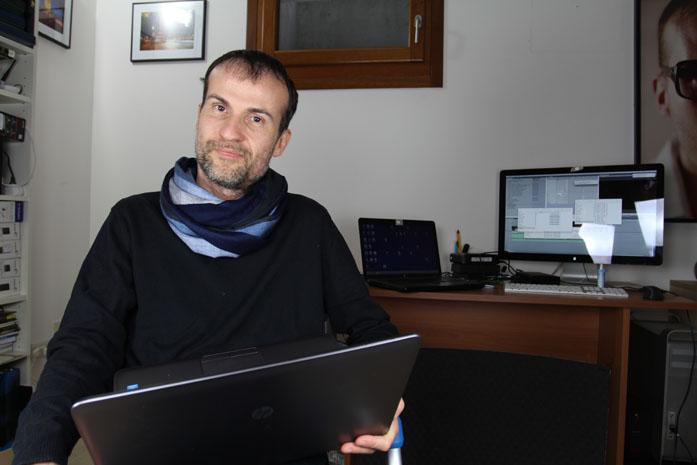Daniele Carrer con il computer portatile nel suo studio