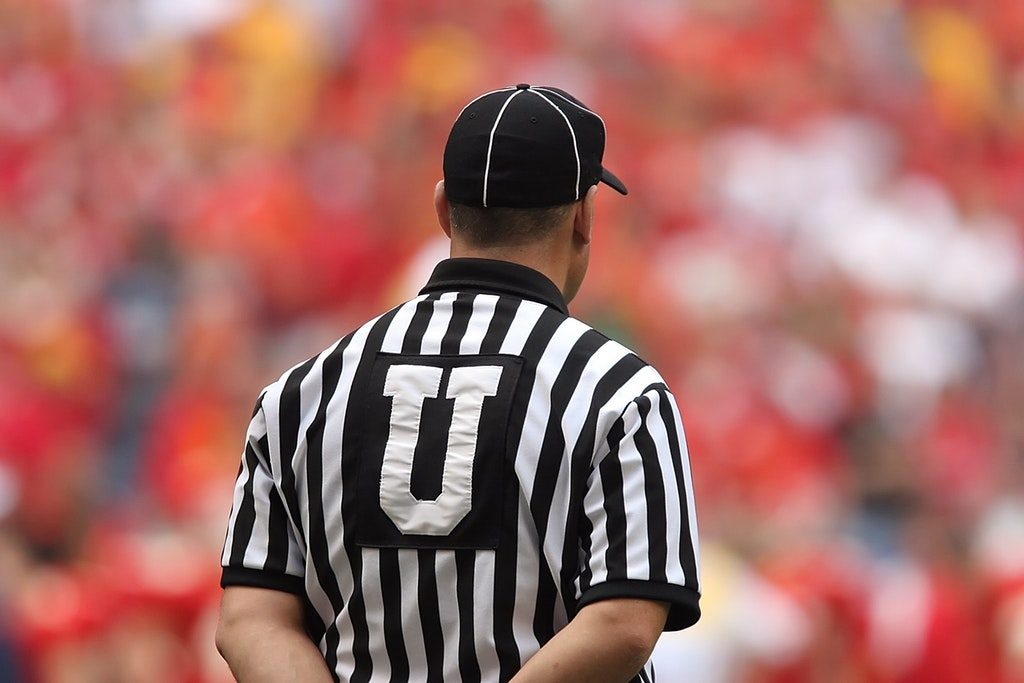 Arbitro di spalle che giudica il match
