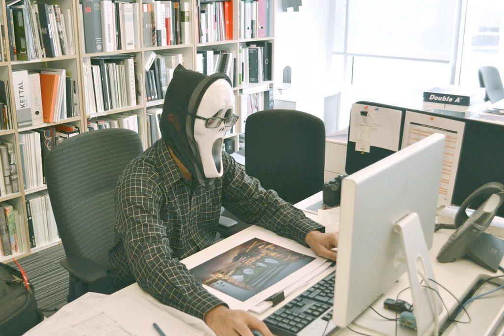 Hacker che ruba stock images e stock footage davanti ad un computer portatile