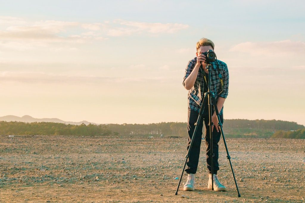 Video maker che effettua una ripresa con reflex e cavalletto