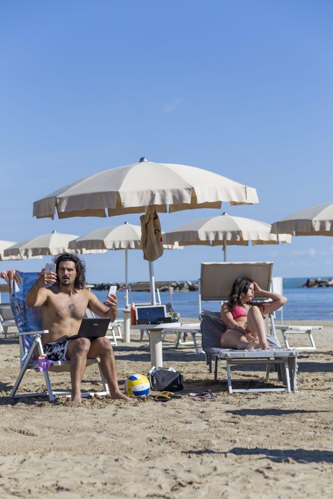 Foto in una spiaggia raffigurante due persone affette da nomofobia