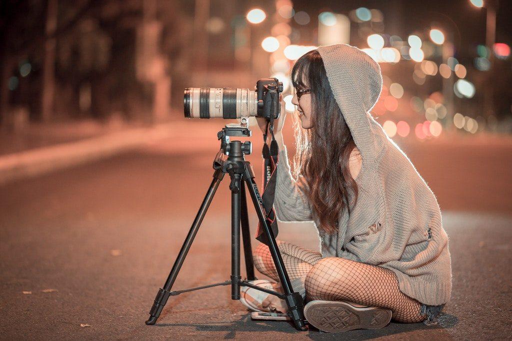 Una filmaker intenta a registrare stock footage con il cavalletto in una strada