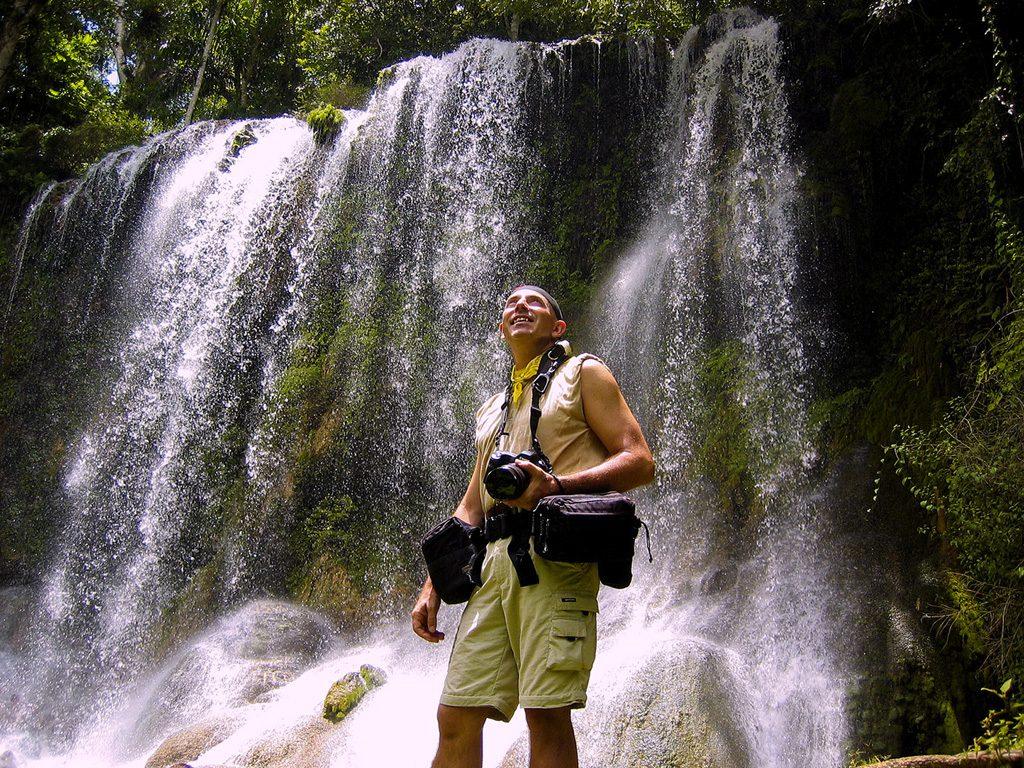Il fotografo Federico Merenghetti di fronte a una cascata a Cuba