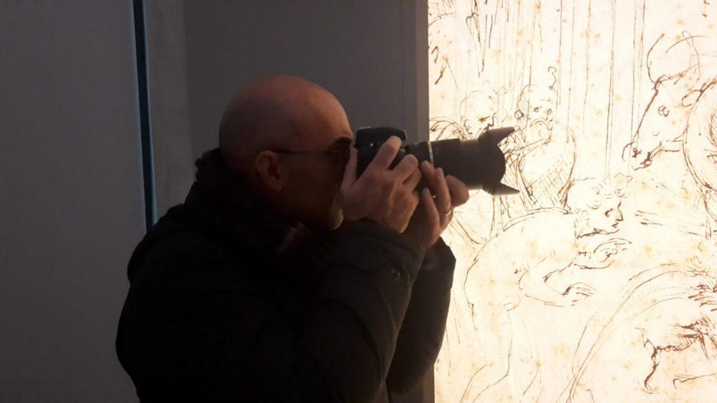 Il fotografo Mauro Celeghini ad una mostra mentre fotografa