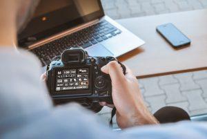 Fotografo che guarda la reflex di fronte al proprio computer portatile