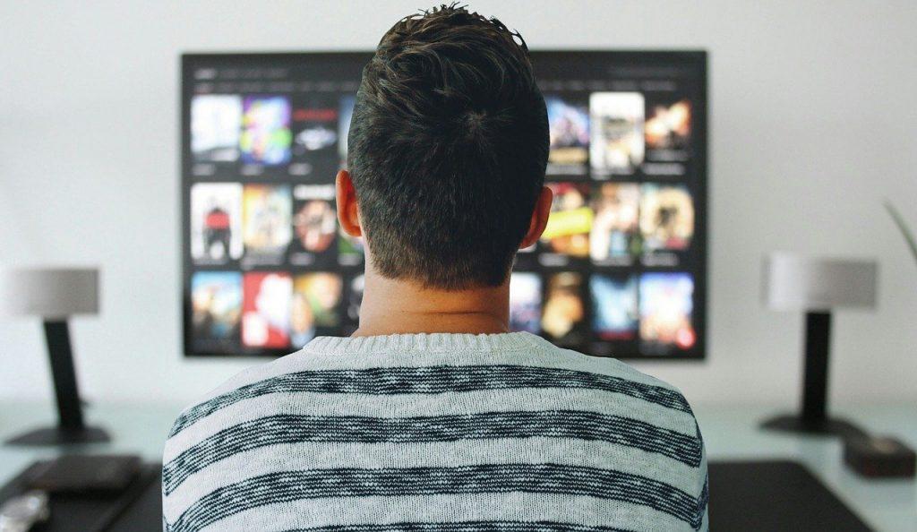 Persona davanti al televisore che guarda un blue ray