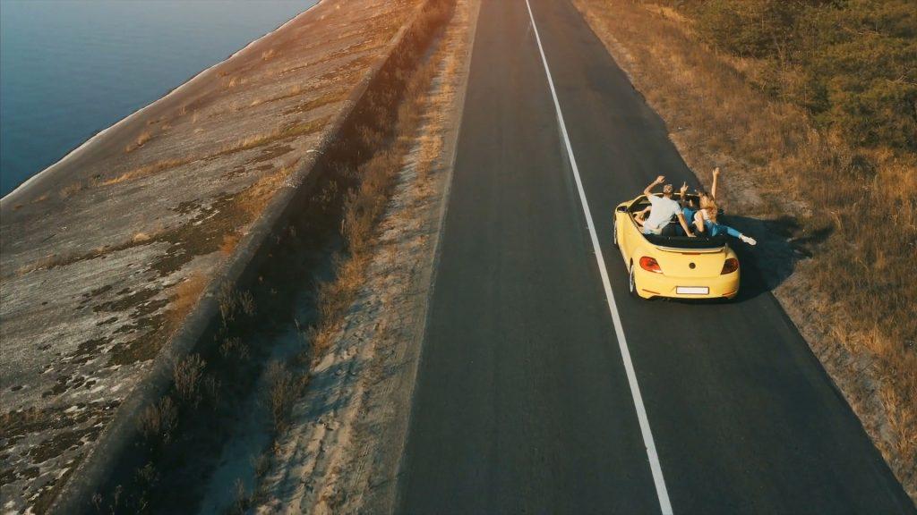 Foto aerea di un'auto con dei giovani all'interno