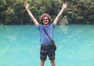 Il fotografo Fabrizio Misson in riva a un lago con l'acqua turchese