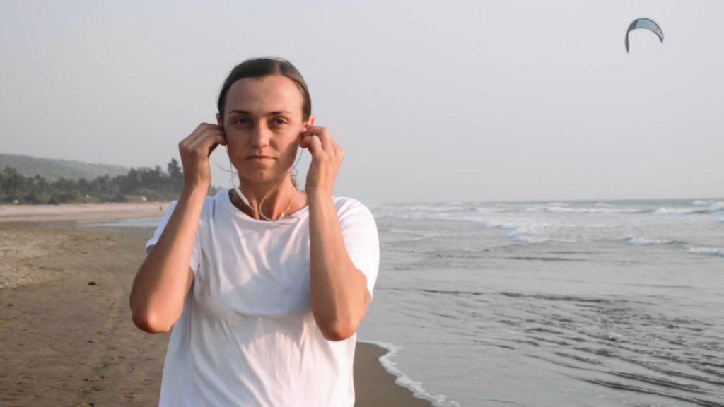Donna che ascolta un audiolibro mentre corre in spiaggia