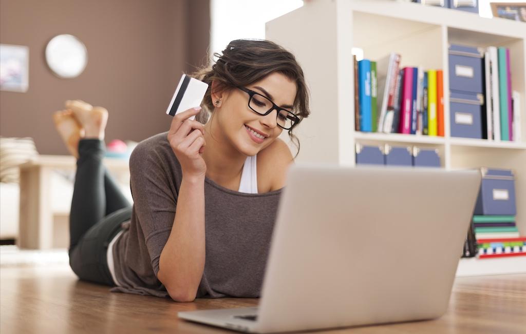 Immagine stock di una donna che fa un acquisto con una carta di credito in mano
