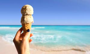 Immagine stock di un gelato in mano a una donna in riva al mare